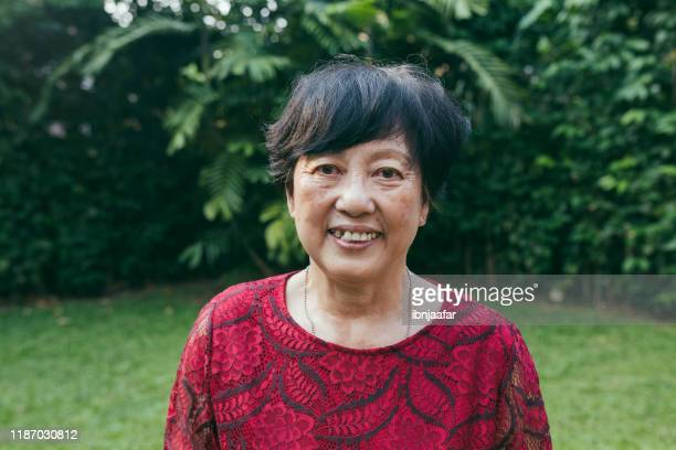 attractive senior chinese woman smiling - ibnjaafar stock photos and pictures