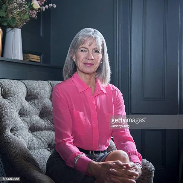 Attraktive leitender Frau in Rosa Bluse, lächelt in die Kamera.