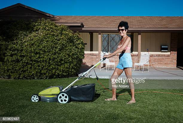 attractive senior woman mowing lawn in bikini top. - tempe arizona stock pictures, royalty-free photos & images