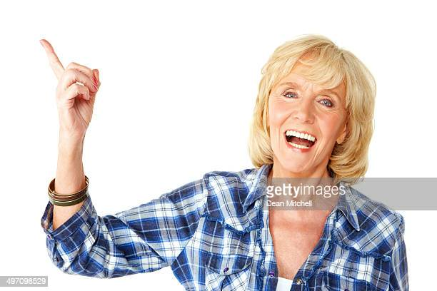 Attractive senior woman pointing at copyspace