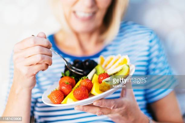attractive senior woman with fruit lunch - healthy eating stock pictures, royalty-free photos & images