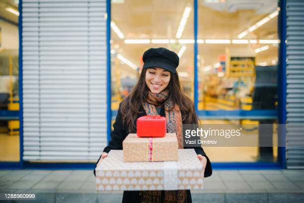 attractive smiling caucasian woman holding presents in front of a big store. - large group of objects stock pictures, royalty-free photos & images