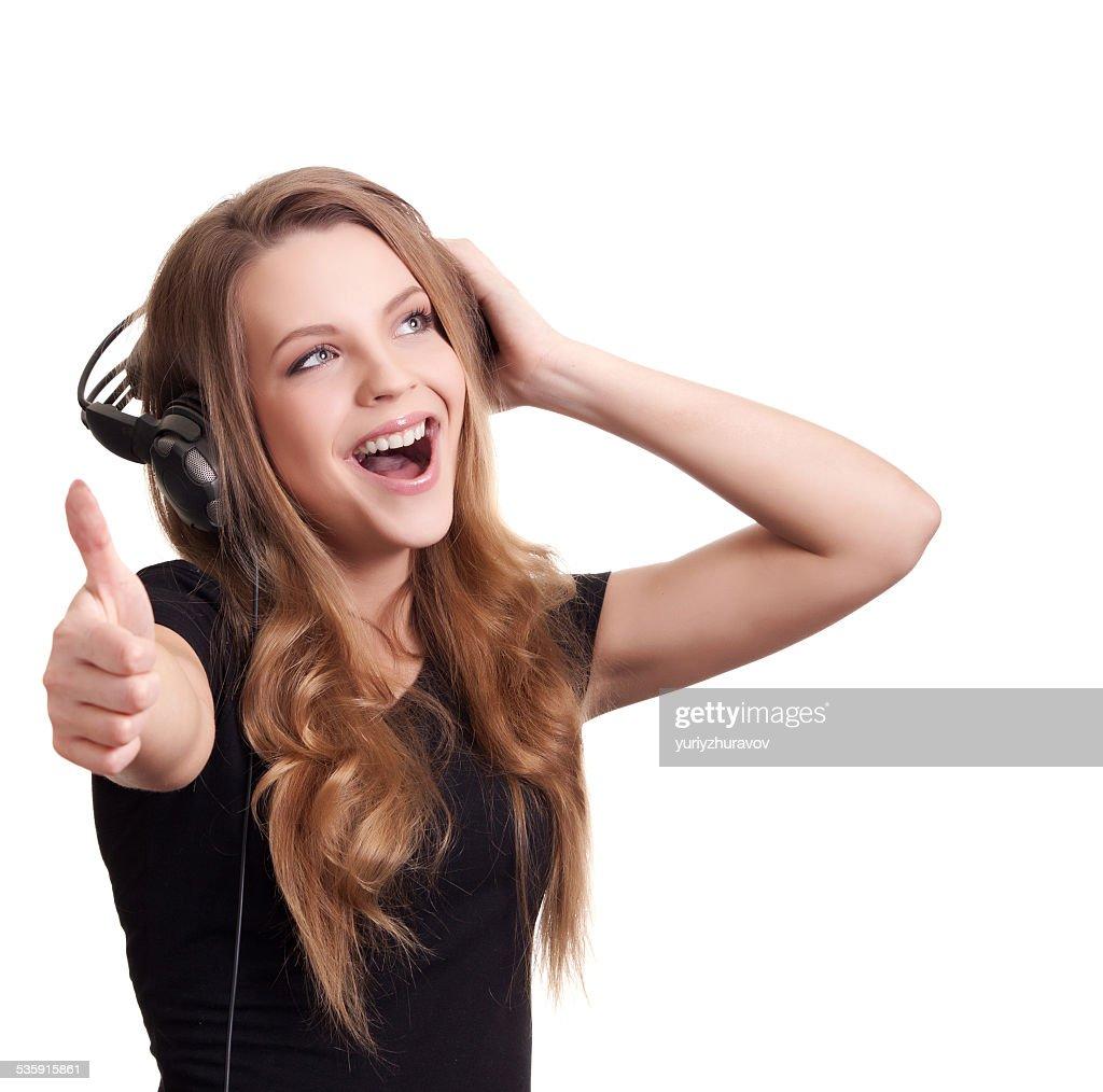 Atraente mulher sorridente com auscultadores sobre fundo branco : Foto de stock