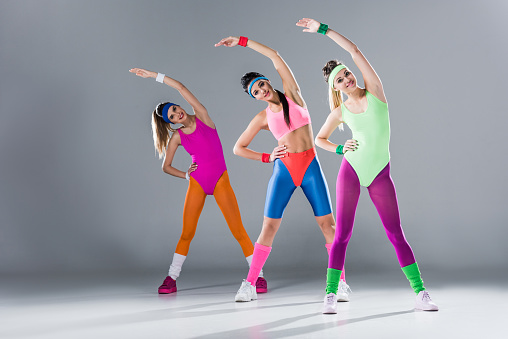 attractive sporty girls in bodysuits training at aerobics workout on grey 1064119338