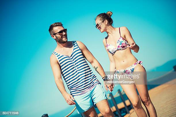 Attractive Summer Couple how Holding Hands on Wooden Pier