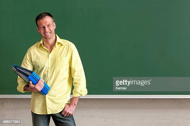 attractive teacher standing smiling at blackboard