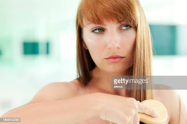 Attraktive Frau, die Ihr Haar Bürsten