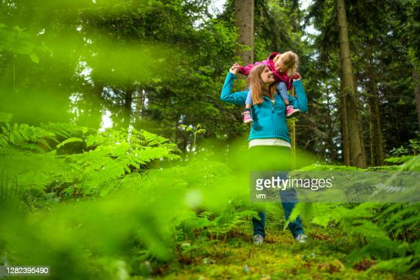 attractive woman carrying little girl on shoulders. - reality fernsehen stock pictures, royalty-free photos & images