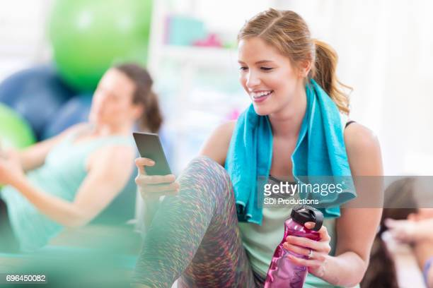 Attractive woman checks her phone after a workout