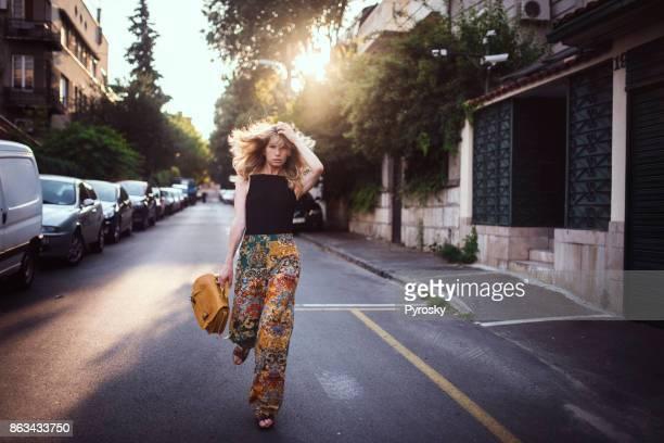 Jolie femme traversant la rue à la hâte