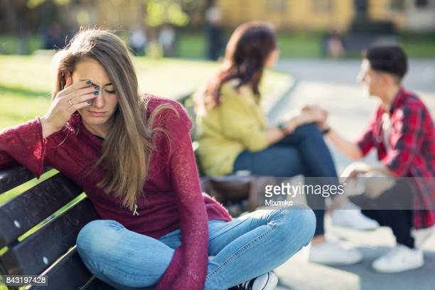Attractive woman crying in the park and ignoring one happy couple