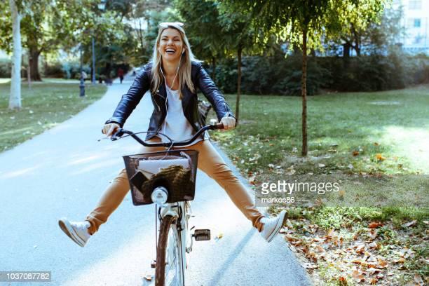jolie femme conduire un vélo dans le parc - être en mouvement photos et images de collection