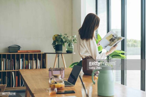 attractive woman enjoying weekend leisure time alone at home - magazine stock pictures, royalty-free photos & images