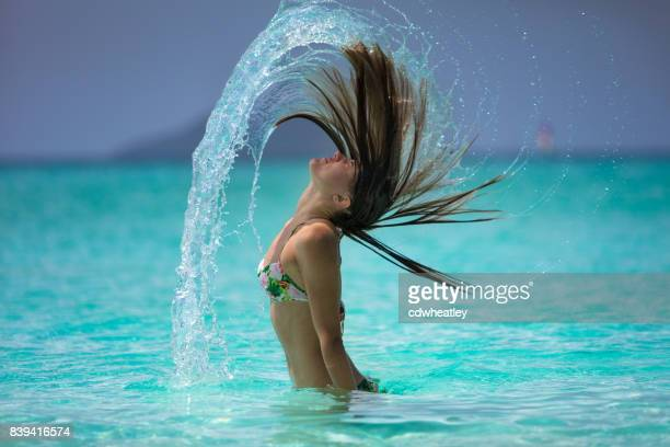 attractive woman flipping hair on a tropical beach in the caribbean