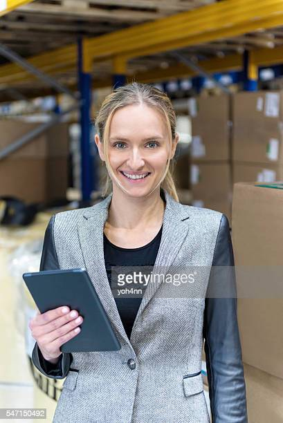 Attractive woman holding tablet in warehouse