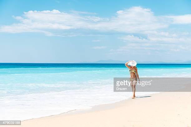 Attractive woman in bikini walking on Maldives beautiful beach