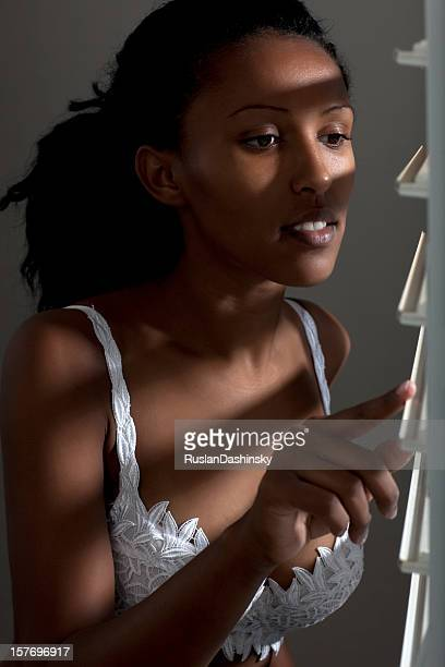 Attractive woman in bra looking out window.