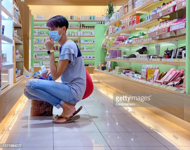 attractive woman in face mask crouching at make-up display shelf contemplating which beauty product to buy for herself - stock photo - face mask beauty product stock pictures, royalty-free photos & images