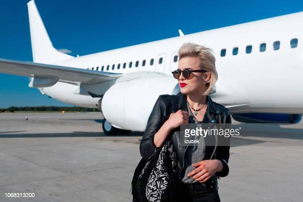attractive woman in front of airplane - getting out stock pictures, royalty-free photos & images