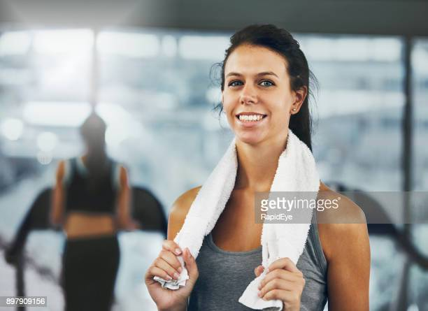 attractive woman in gym gives a challenging smile - genderblend stock pictures, royalty-free photos & images