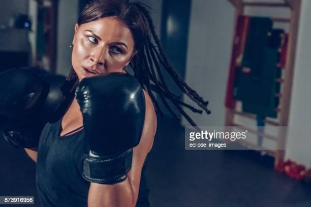 aantrekkelijke vrouw in sportschool met bokshandschoenen op - extra groot stockfoto's en -beelden