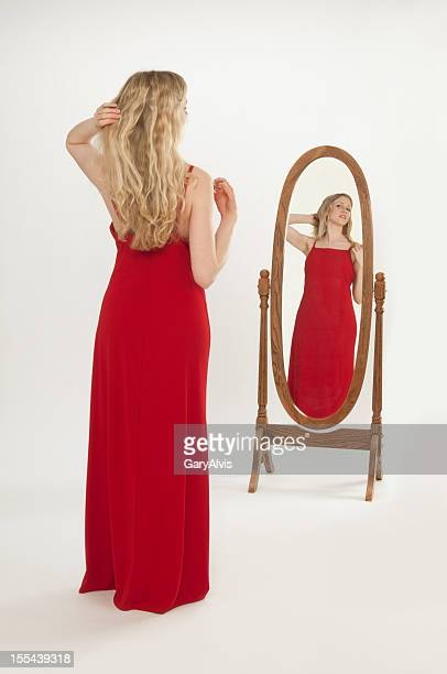Attractive woman in red evening gown, primping-reflection in mirror