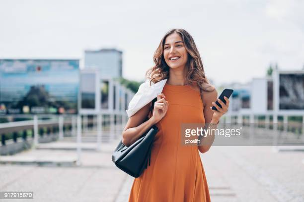 attractive woman in the city - orange dress stock pictures, royalty-free photos & images