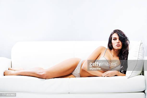 Attractive woman in underwear lying on sofa.