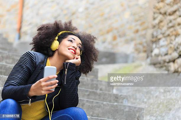 Attractive woman listening music sitting on stairs