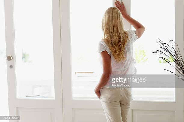 attractive woman looking out through window - free images stock pictures, royalty-free photos & images
