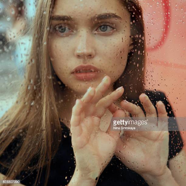 Attractive woman near the window covered with raindrops