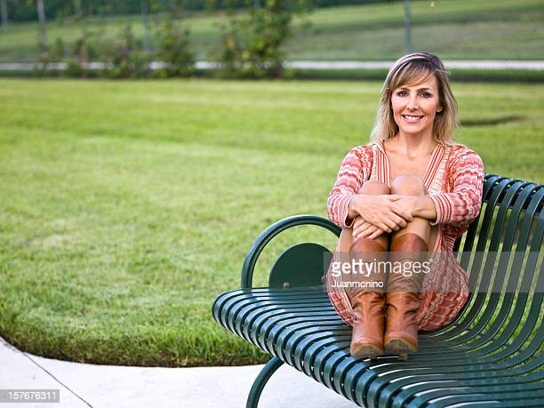 attractive woman on park bench - cougar woman stock photos and pictures