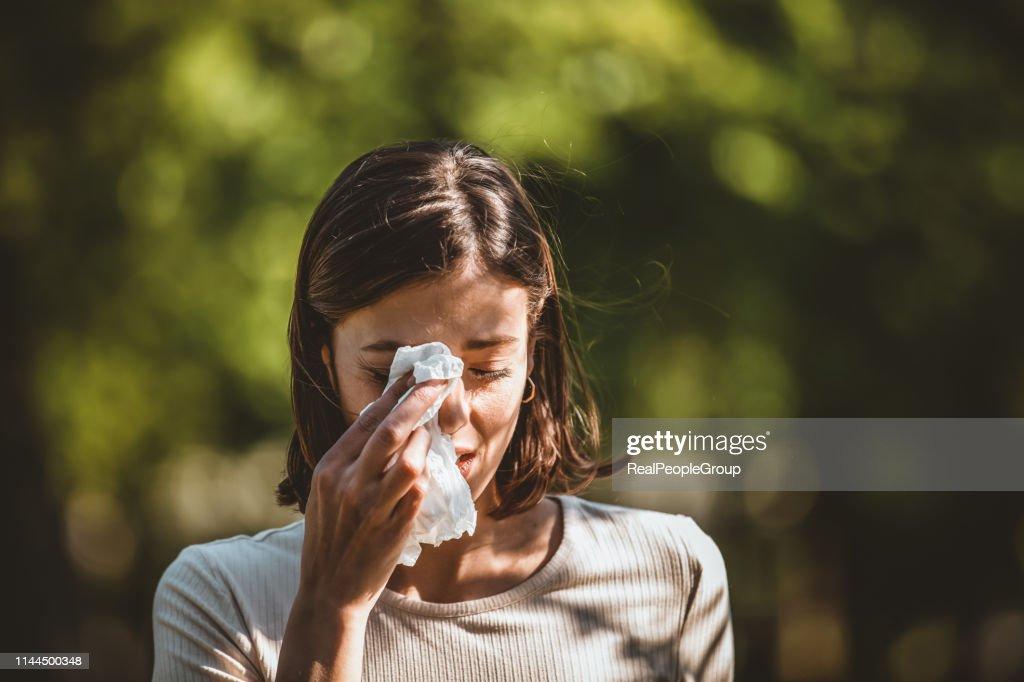 A mulher atrativa ao ar livre está tendo a alergia : Foto de stock