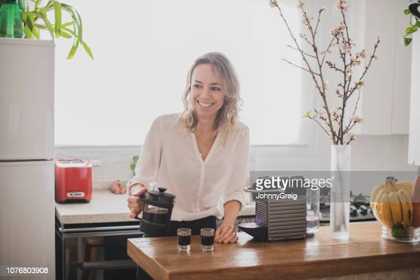 attractive woman pouring espresso in kitchen - coffee maker stock pictures, royalty-free photos & images