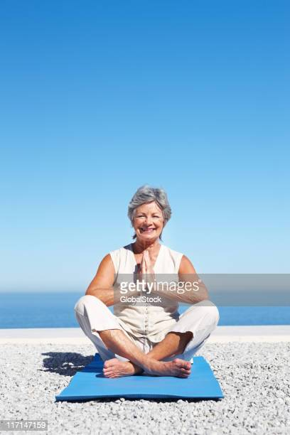 Attractive woman sitting on exercise mat doing yoga