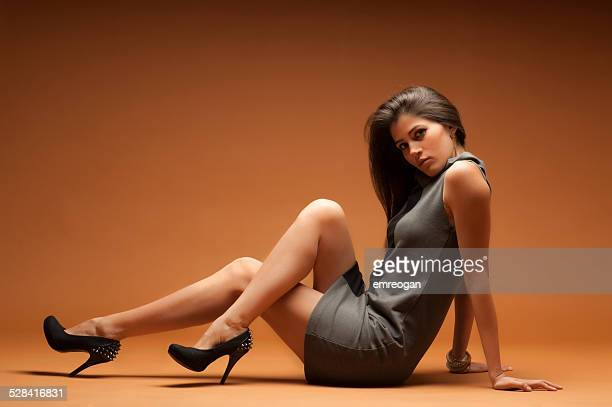 attractive woman sitting on floor - long legs women stock photos and pictures
