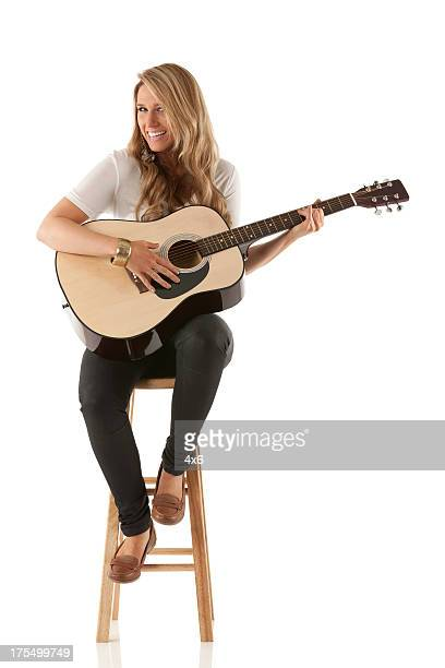 attractive woman sitting on stool and playing a guitar - acoustic guitar stock pictures, royalty-free photos & images