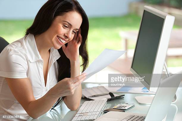 Attractive woman smiling reading a document