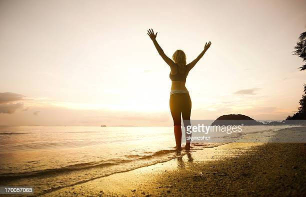 Attractive woman standing against the beautiful sunset.