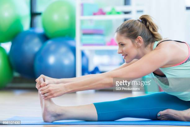 Attractive woman stretches at the gym