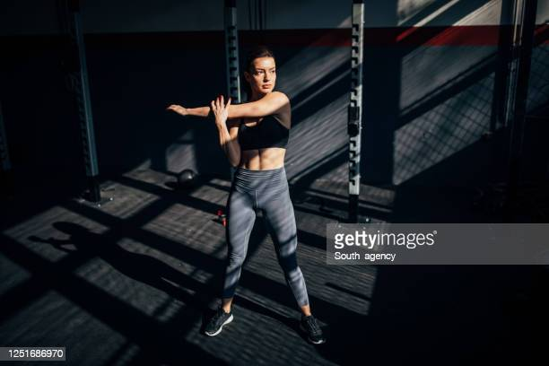 attractive woman stretching in the gym - trousers stock pictures, royalty-free photos & images