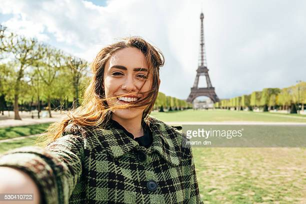 Attractive woman taking selfie in front of the Eiffel tower