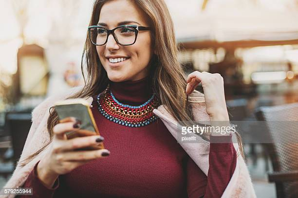 Attractive woman texting in restaurant