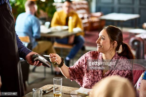 attractive woman using contactless technology in cafe - paying stock pictures, royalty-free photos & images
