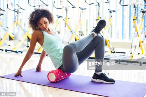 attractive woman using massage roller at the gym - massage black woman stock photos and pictures