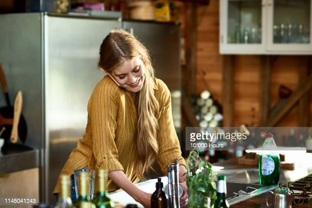 attractive woman using phone and doing dishes - good news stock pictures, royalty-free photos & images