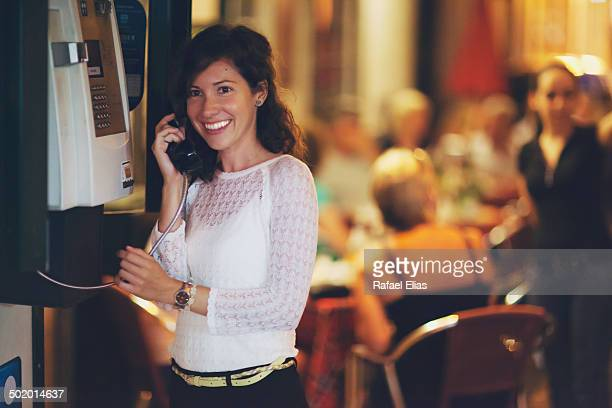 Attractive woman using public telephone