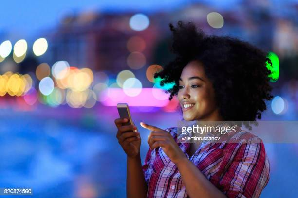 Attractive woman using smart phone at night on street