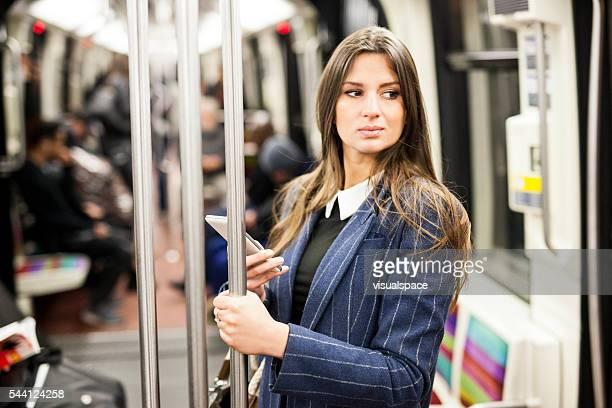 Attraktive Frau benutzt Smartphone während der U-Bahn