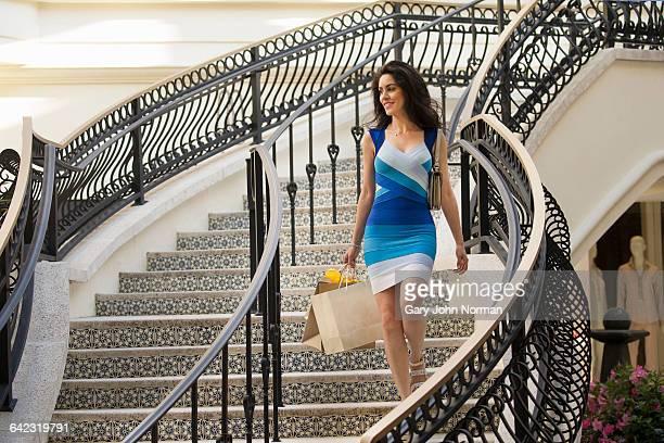 attractive woman walking down tiled staircase - palm beach county stockfoto's en -beelden